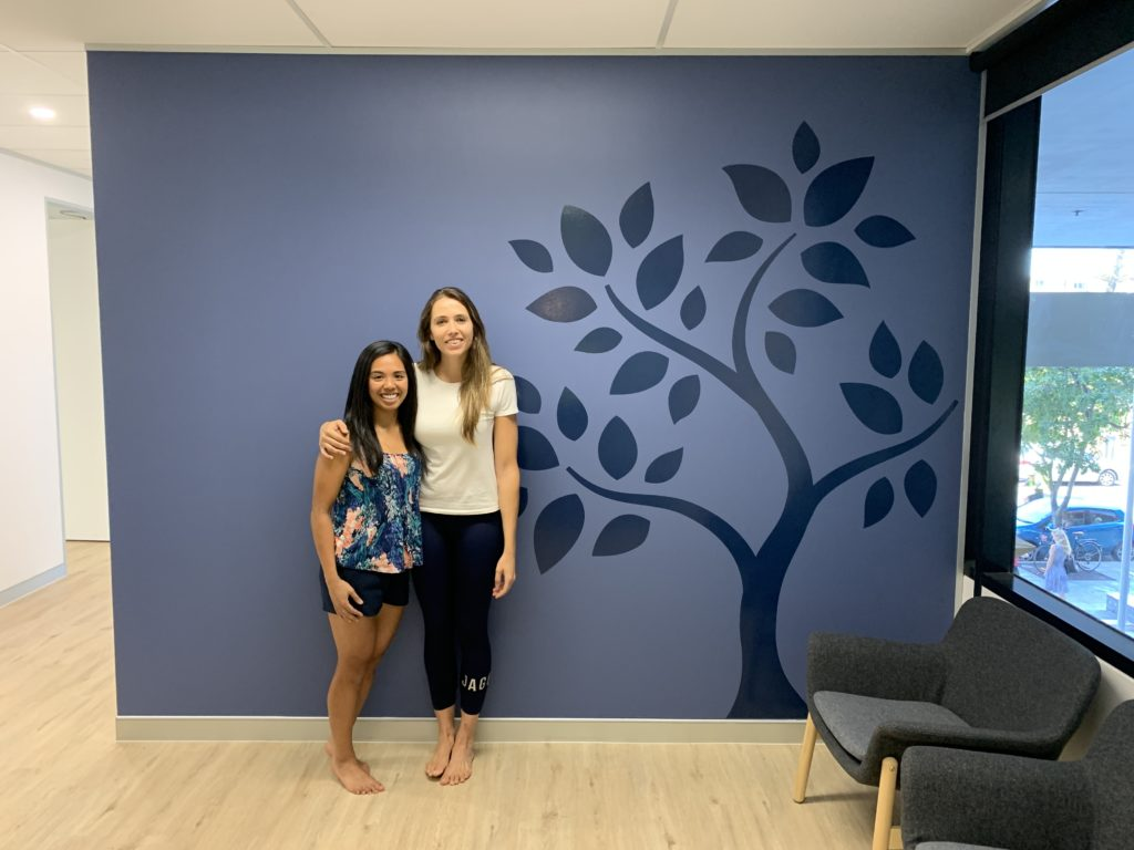 Co-Owners Andrea Mendoza and Alexane Escot in front of clinic feature wall at The Scoliosis Collective