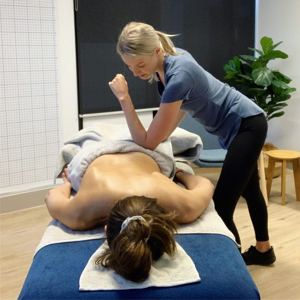 myotherapist performing manual release technique on a client's pelvis muscles